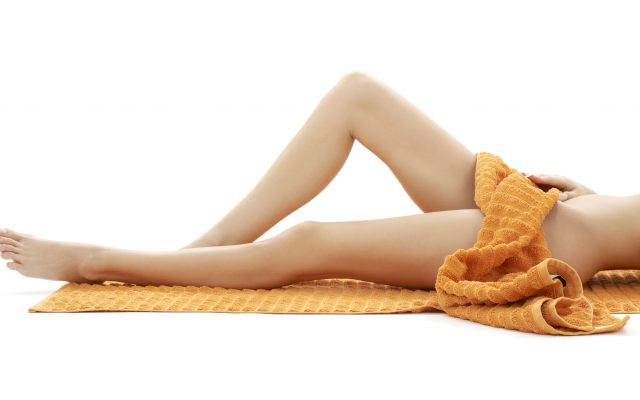 long legs of relaxed lady with orange towel over white